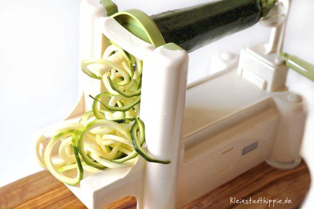 Zucchini und Karotten durch den Spiralschneider drehen